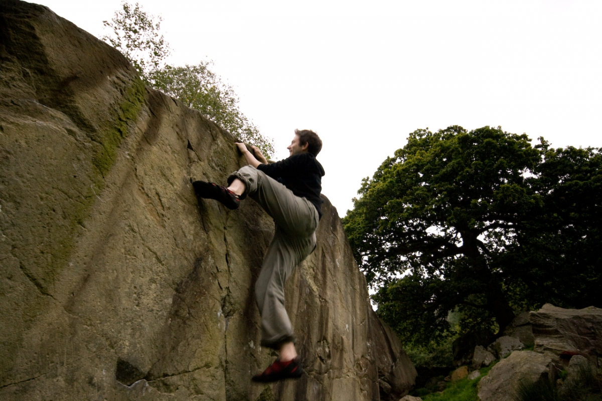 Image of a rock climber almost to the top of the cliff.  Example of grit.
