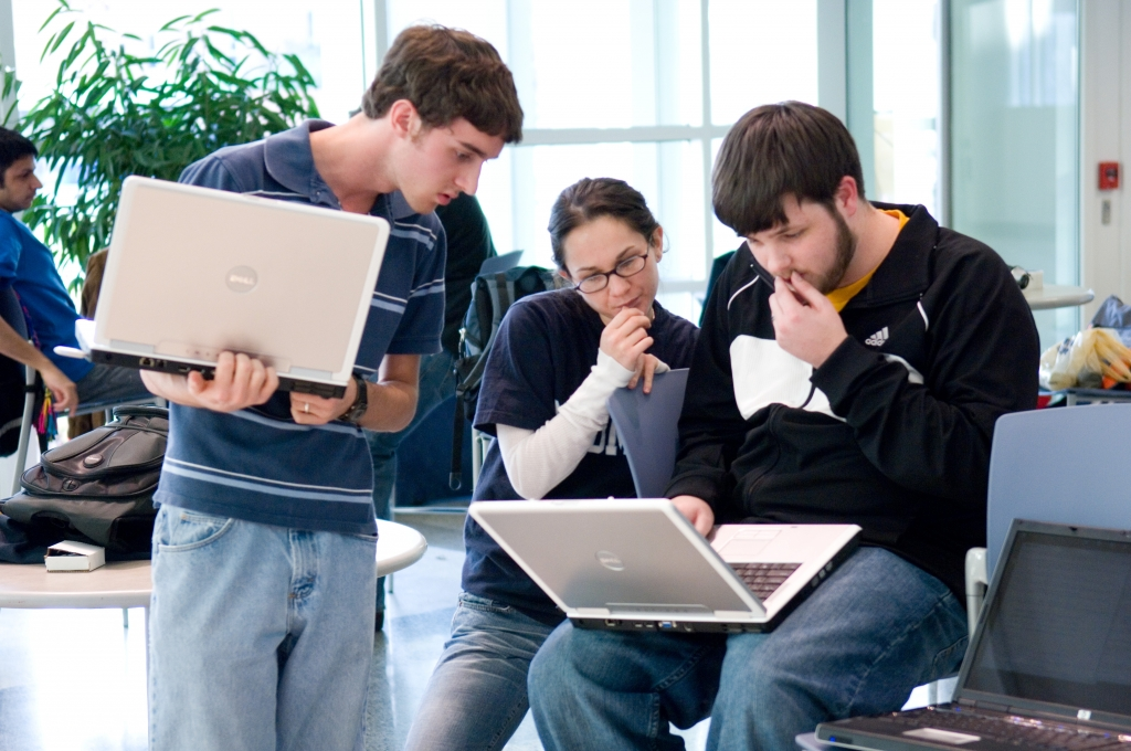 Three people looking a laptop