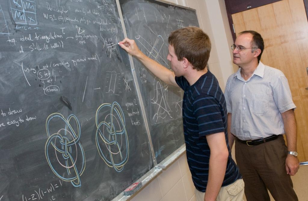 Student writes on chalkboard as teacher oversees